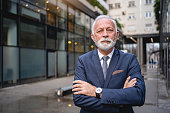 Frowned serious senior businessman with arms crossed standing in front of his company