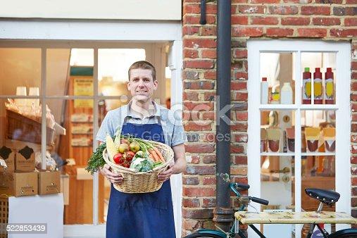istock Proud shop keeper holding basket of vegetables 522853439