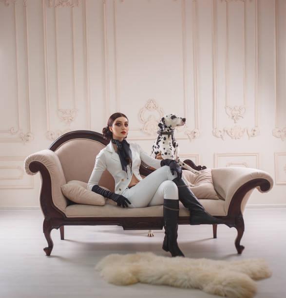 stolz, kräftig, stilvoll, mädchen jäger, in kostüm reitende frau posiert mit einem dalmatinischen hund. hintergrund ist klassisches sofa, wände mit formteilen. make-up smokey augen, strenge, kreative frisur bagels. - königin kopfteil stock-fotos und bilder