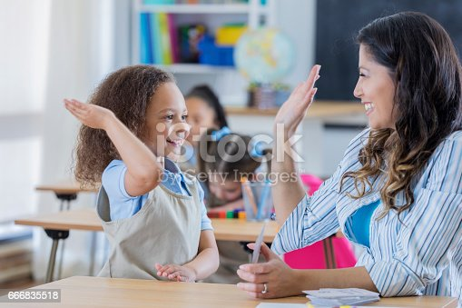 istock Proud teacher gives student a high five in math class 666835518