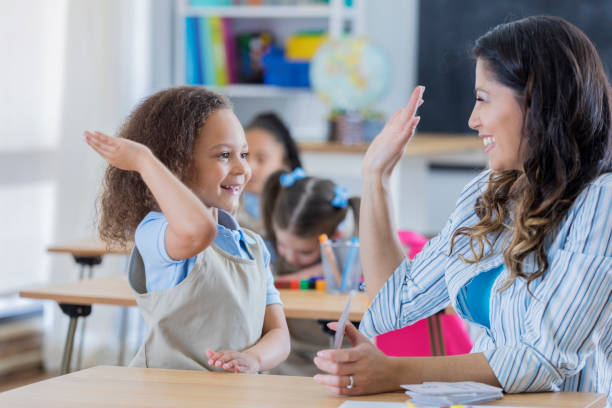 Proud teacher gives student a high five in math class stock photo