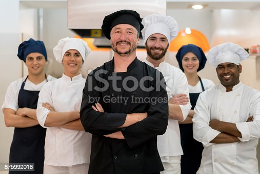 Proud multi ethnic team of chef, sous chefs and cooking assistants looking at camera smiling with arms crossed