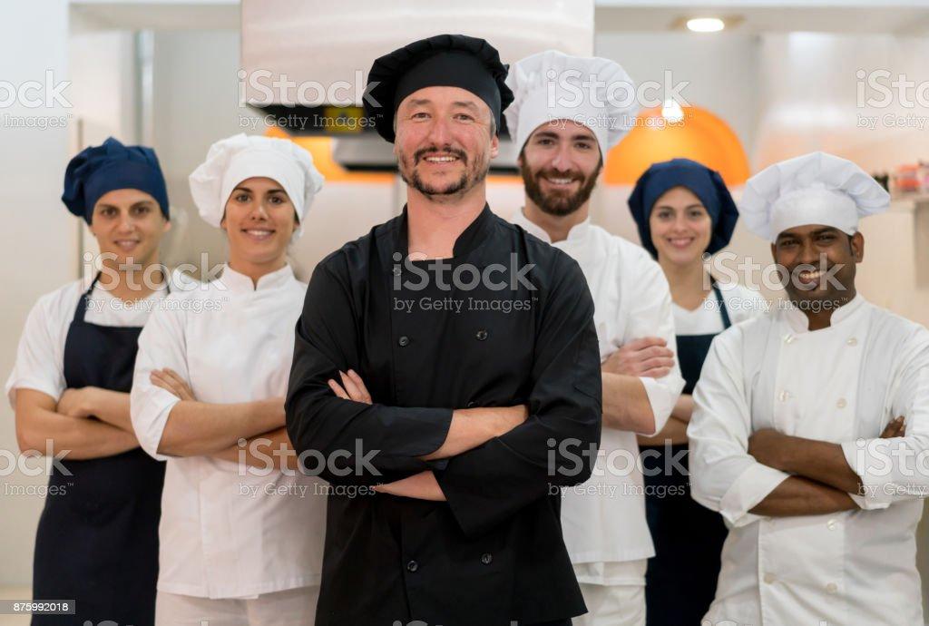 Stolze Team von Küchenchefs, Sous Chefs und Kochen Assistenten Blick auf die Kamera zu Lächeln – Foto