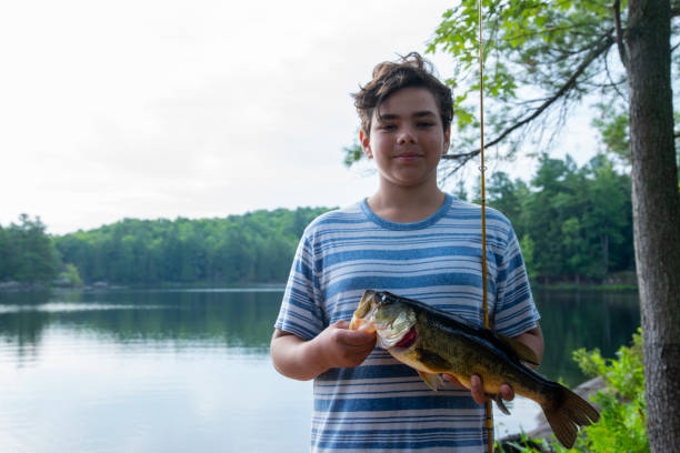 A proud teen fisherman with a nice Largemouth bass he has caught (real) stock photo