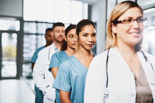 Portrait of a young nurse standing in a line amongst her colleagues in a hospital