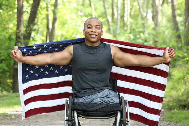 proud to be American African american man sitting in wheelchair and holding out a flag at the park happy 4th of july photos stock pictures, royalty-free photos & images
