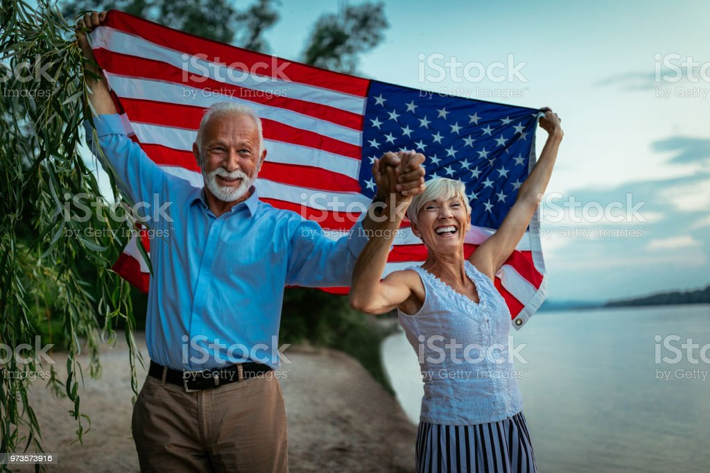Proud to be an American Shot of a happy senior couple walking by the river with an American flag 1960-1969 Stock Photo
