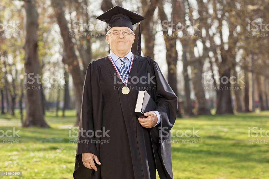 Proud university dean posing in a park stock photo