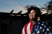 Proud woman raising the flag of the United States of America