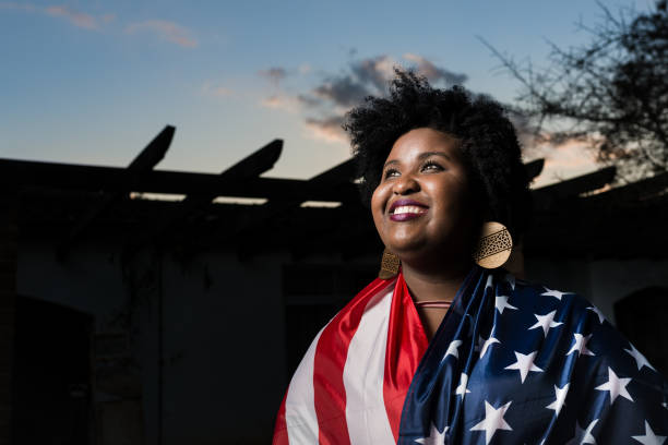 Proud woman raising the flag of the United States of America stock photo