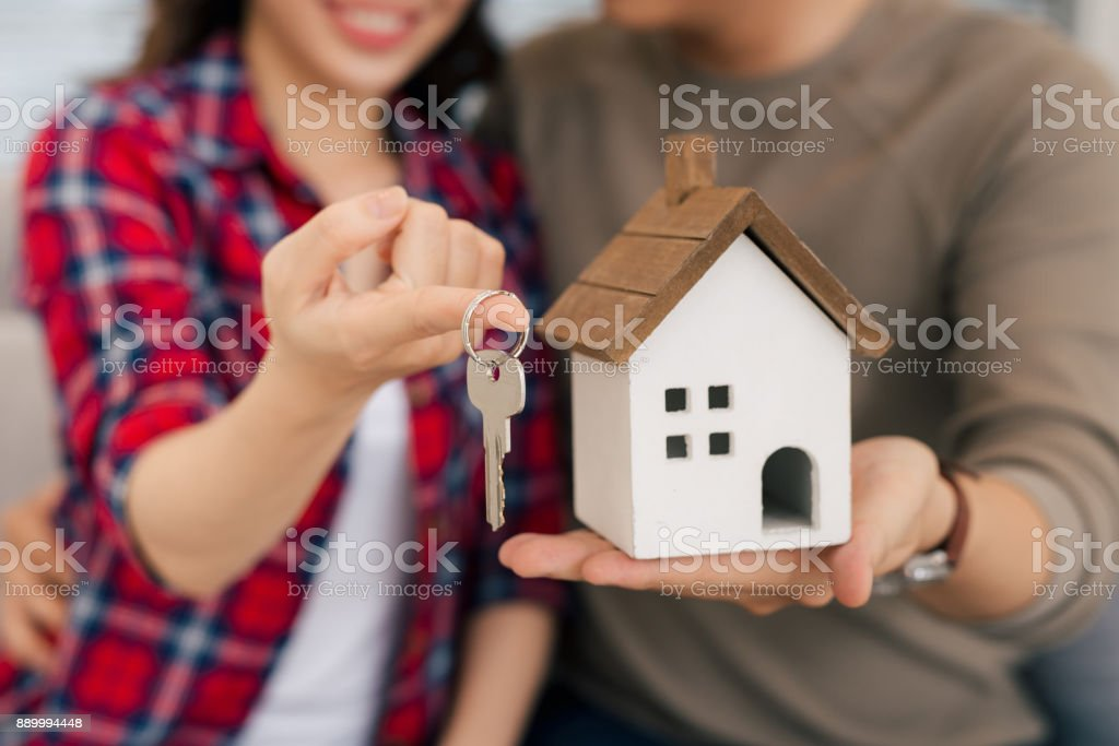 Proud young asian couple with keys and wooden house modelling stock photo