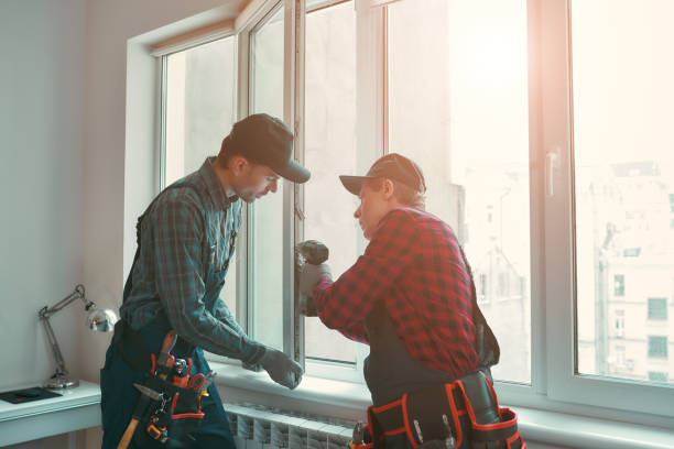 Provading best service. Men are installing a window Portrait of mature men wearing uniform standing indoors and installing new windows in the apartment. Horizontal shot replacement stock pictures, royalty-free photos & images