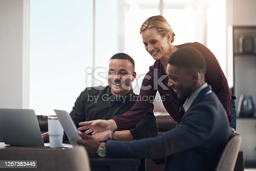 Shot of a group of businesspeople working together on a laptop in an office