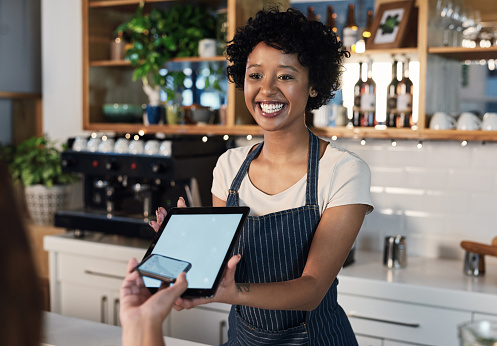 Shot of a young woman accepting a digital payment from a customer in a cafe