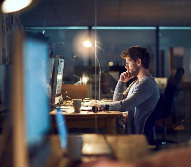 demostrando su dedicación a través del día y la noche - trabajar hasta tarde fotografías e imágenes de stock