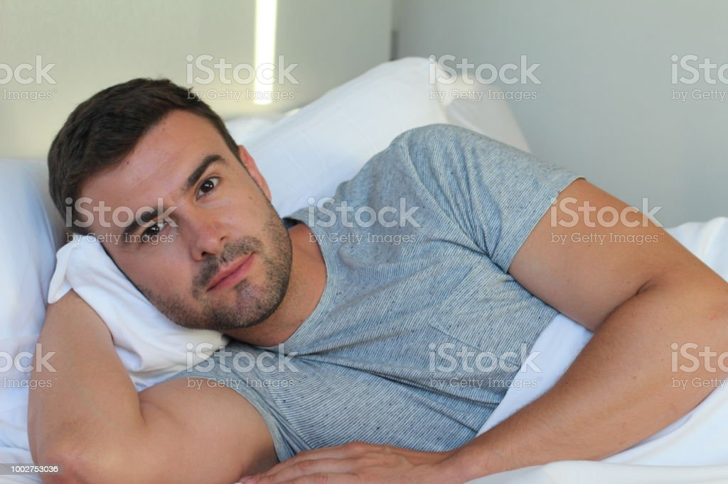 Provocative man staring at camera in bed stock photo