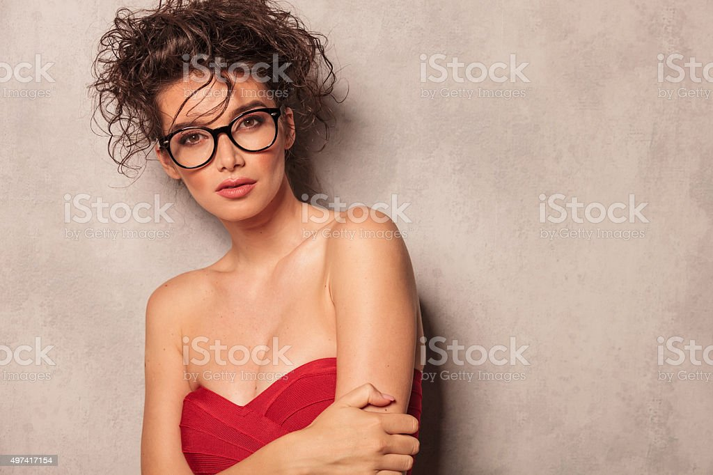 provocative young woman leaning on a grey wal stock photo