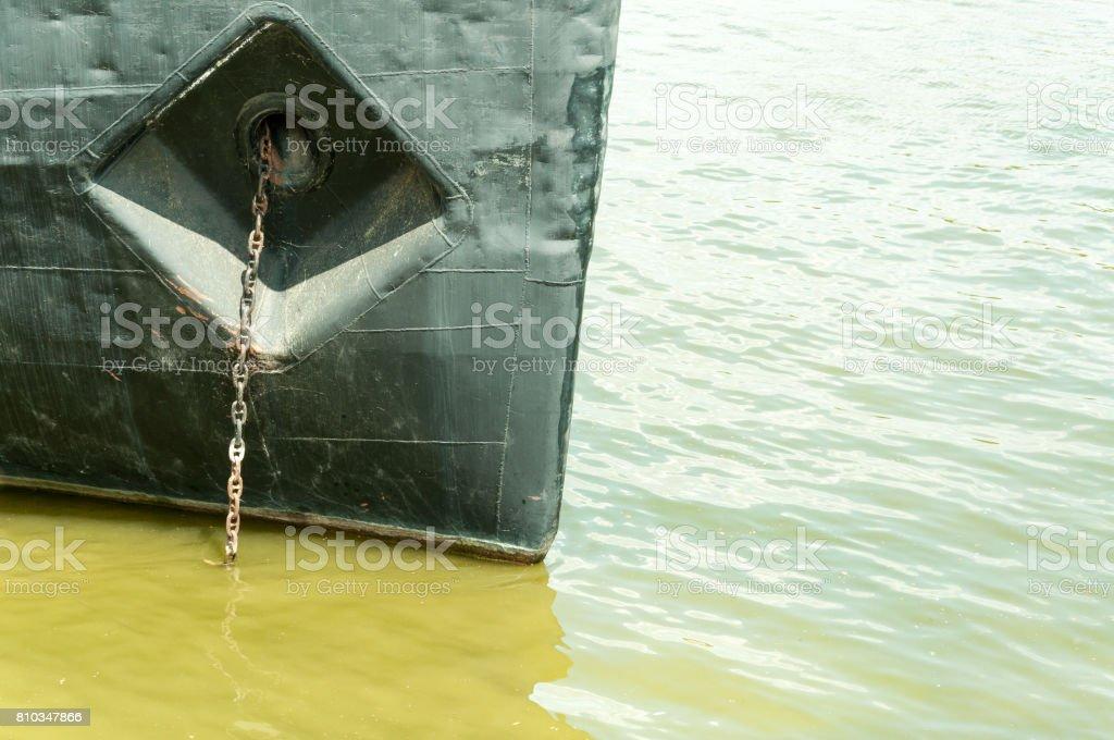 Prow of old rusty dark ship with anchor chain anchored in green Danube river. Novi Sad, Serbia. stock photo
