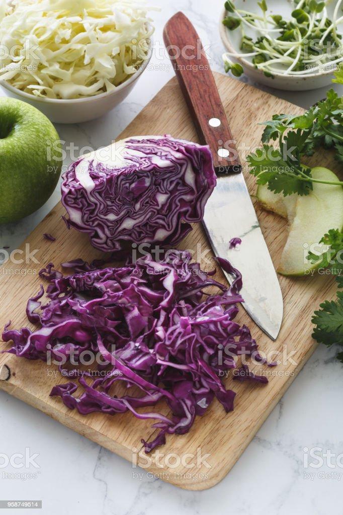 Préparation du Repas avec du Chou Rouge Haché, Chou Blanc, Pomme et Herbes Aromatiques stock photo