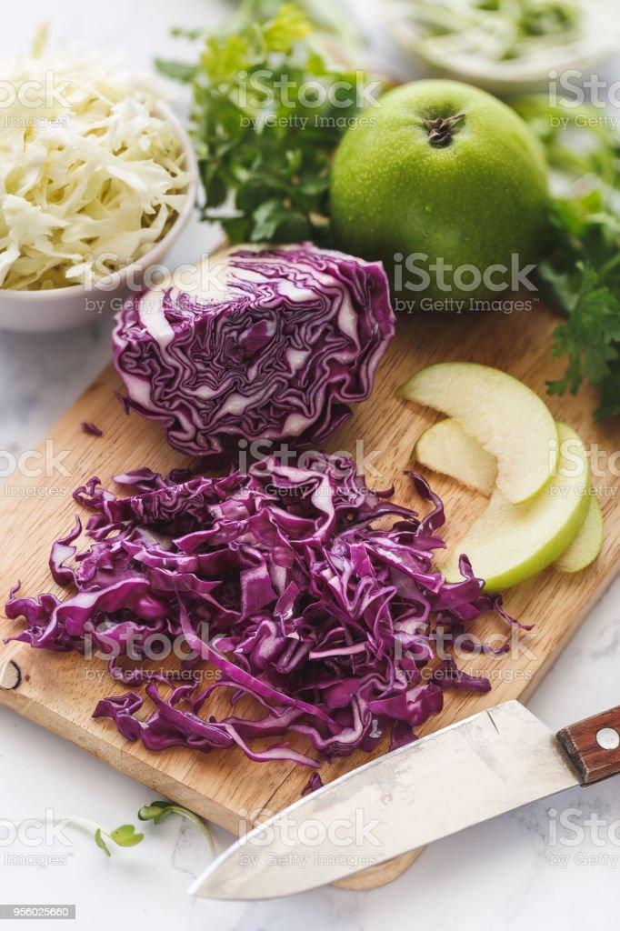 Préparation d'une Salade de Chou Rouge, Chou Blanc, Pomme Verte et Herbes Aromatiques. stock photo