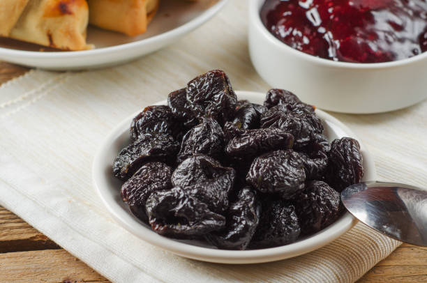Prunes on small plate with jam from the plums on wooden table. Dried Plums. Healthy and vegetarian food stock photo