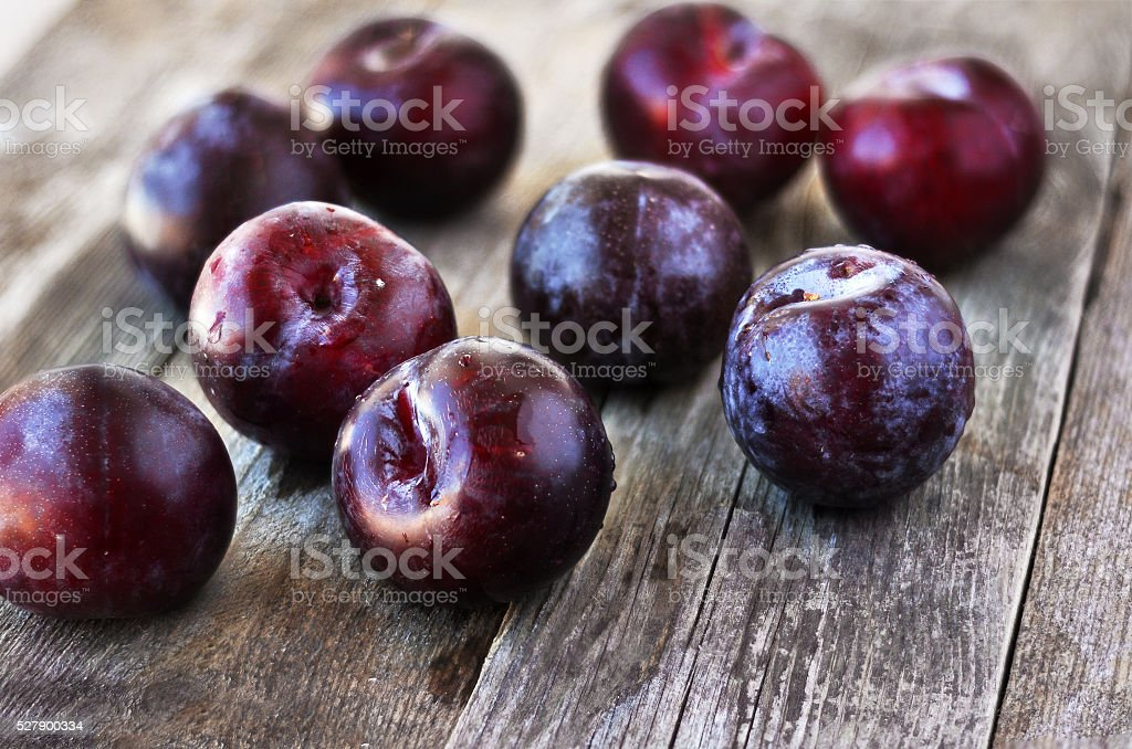 Prunus domestica. Ripe Plums on the wood backgraund. stock photo