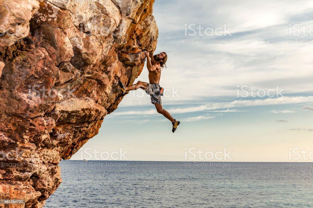 Psicobloc rock climber at the sea stock photo