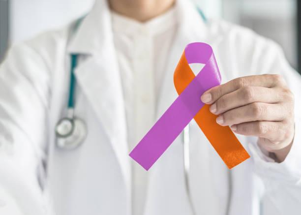 maladie psoriasis et la dermatite eczéma peau maladie sensibilisation campagne concept avec ruban orange violet orchidée symbolique s'incliner couleur sur support main du médecin - psoriasis photos et images de collection