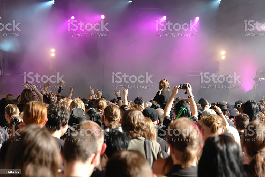 A psyched concert crowd waiting by the foggy and lit stage royalty-free stock photo