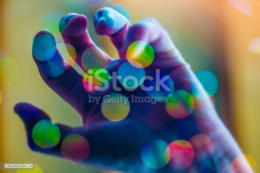 A simple background design showing a psychedelic colored hand reaching up through defocussed vivid bokeh.  A concept design that could represent clubbing, torment, pain, addiction, mental health problems or a struggle in general.
