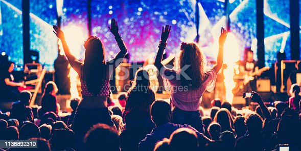 Rear view of two girls waving hands sitting on shoulder at a concert