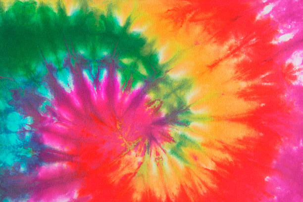 Psychedelic Tie Dye, a 1960s Style Symbol of Peace Background Colorful tie dye fabric with spiral circle pattern in rainbow colors. The free-form pattern is associated with 1960s and 1970s fashion style and a symbol of peace and the peace movement of that era. The multi-colored array of vibrant color was the essence of cool, groovy, psychedelic trends. psychedelic stock pictures, royalty-free photos & images
