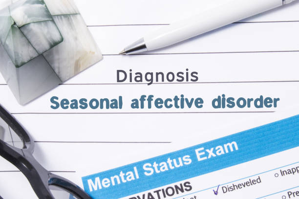 Psychiatric Diagnosis Seasonal Affective Disorder. Medical book or form with name of diagnosis Seasonal Affective Disorder is on table of doctor surrounded by questionnaire to determine mental state Psychiatric Diagnosis Seasonal Affective Disorder. Medical book or form with name of diagnosis Seasonal Affective Disorder is on table of doctor surrounded by questionnaire to determine mental state affective stock pictures, royalty-free photos & images