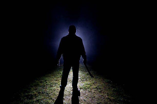 Psycho Killer - Machette Dark, foggy outdoor silhoette of a man wearing a leather jacket, knit cap and gloves holding a machette. creepy stalker stock pictures, royalty-free photos & images