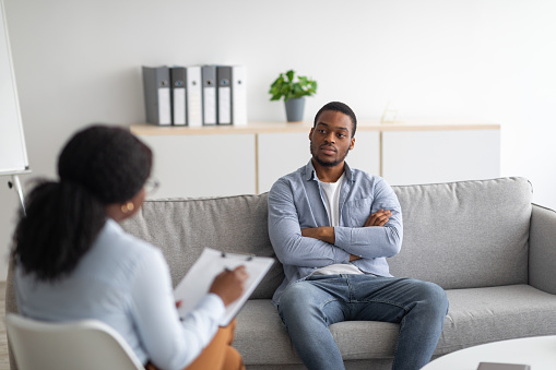 Psychological counselling. Black male patient with depression having session with psychotherapist at office. African American man with PTSD consulting mental health professional at clinic