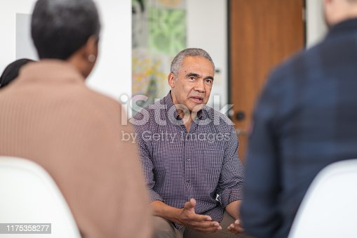 A multi-ethnic group of adults are attending a group therapy session. The attendees are seated in chairs arranged in a circle. The psychologist is a mature adult black man. He is talking to the group. He has a serious expression on his face.