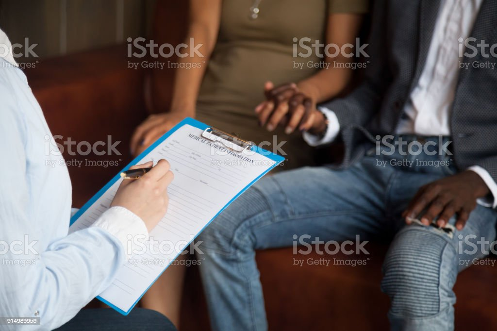 Psychologist filling medical patient information form consulting african couple, closeup stock photo