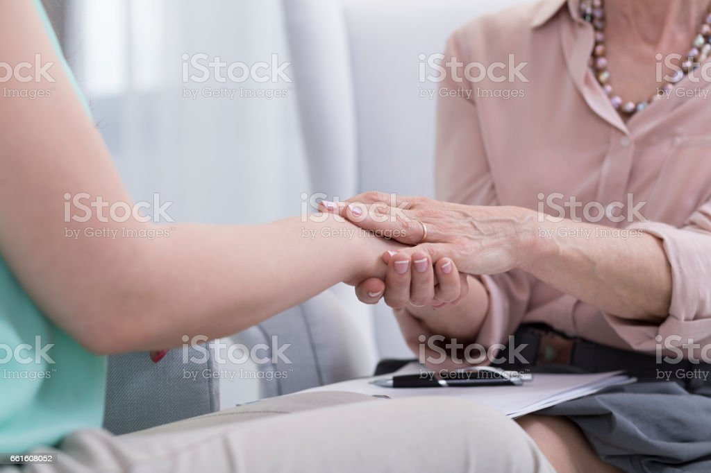 Psychologist holding her patient's hand stock photo
