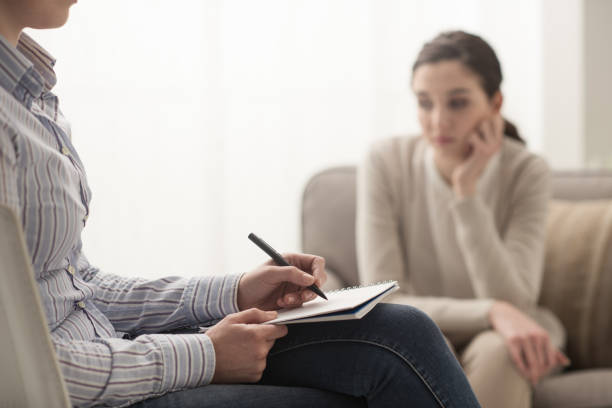 psychologist listening to her patient - psychiatrist stock photos and pictures