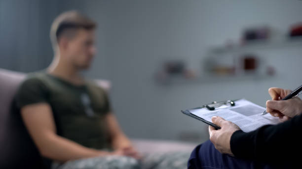 Psychologist making notes during therapy session with sad male soldier, PTSD Psychologist making notes during therapy session with sad male soldier, PTSD mental health stock pictures, royalty-free photos & images