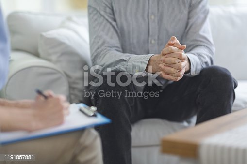 Psychologist taking notes while conversation with patient at psychotherapy session, close up