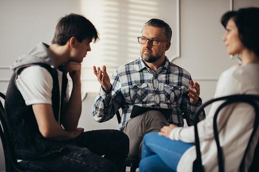 Psicólogo Hablando Con El Adolescente Deprimido Y Su Madre Durante La Sesión De Terapia Foto de stock y más banco de imágenes de Adicción