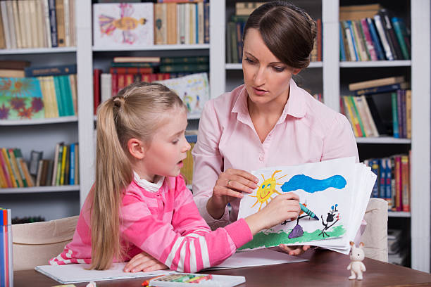 Psychologist talks with girl about a drawing stock photo