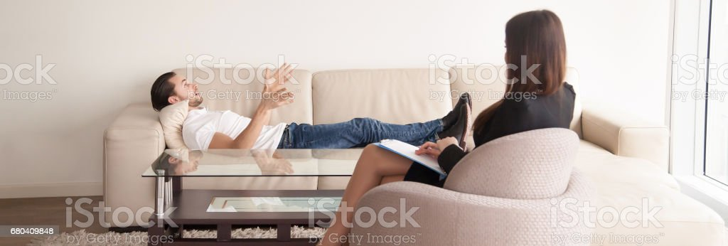 Psychologists office, male patient talking about problems to female psychotherapist stock photo