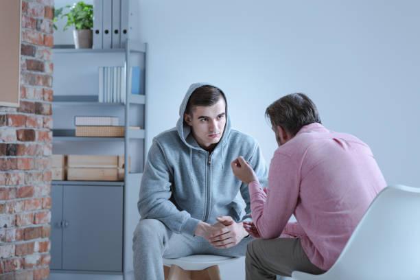 uno specialista di psicologia che spiega un piano d'azione per il recupero a un adolescente in difficoltà durante una sessione di terapia individuale. - assuefazione foto e immagini stock