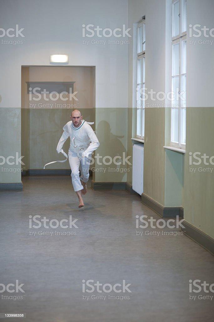 Psychopath into a straightjacket runs away royalty-free stock photo