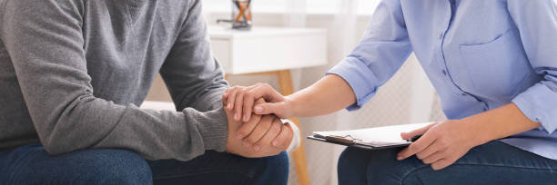 Psychotherapist supporting her depressed patient close up stock photo