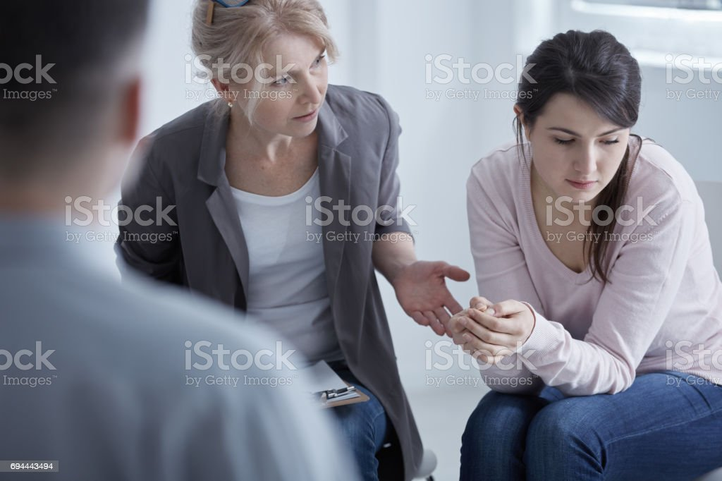 Psychotherapist supporting young woman stock photo