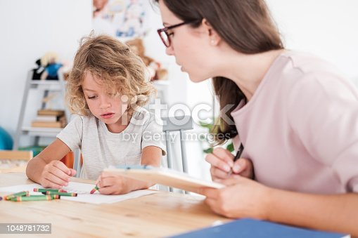 istock A psychotherapist watching a child draw pictures with crayons during an evaluation in a private school. 1048781732