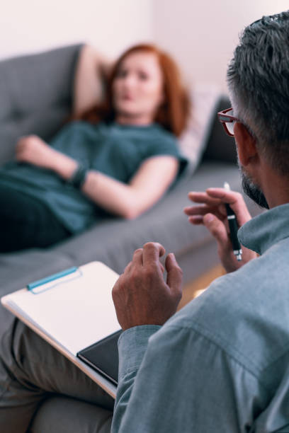 Psychotherapist with notes talking with client during therapy Psychotherapist with notes talking with client during therapy drug rehab stock pictures, royalty-free photos & images
